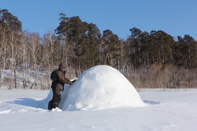 Homem na roupa morna que constrói um iglu em uma clareira nevado no inverno, Sibéria, Rússia foto de stock