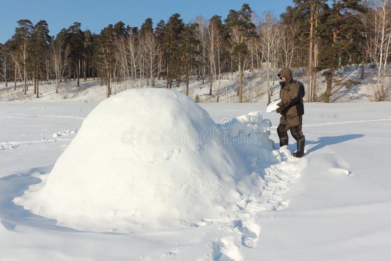 Homem na roupa morna que constrói um iglu em uma clareira nevado no inverno, Sibéria, Rússia imagens de stock