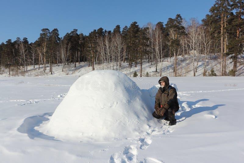 Homem na roupa morna que senta-se por um iglu em uma clareira no inverno, Sibéria, Rússia imagens de stock royalty free