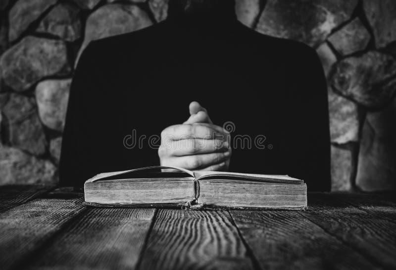 Homem na roupa preta na frente de um livro aberto velho fotografia de stock royalty free