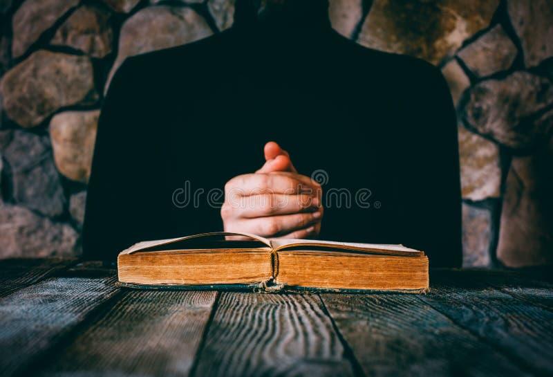 Homem na roupa preta na frente de um livro velho aberto imagem de stock royalty free