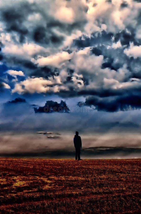 Homem na roupa preta que está no horizonte sob a nuvem do datk fotos de stock
