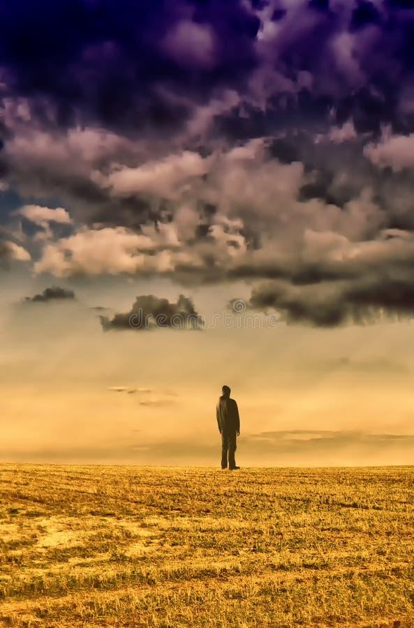 Homem na roupa preta que está no horizonte sob a nuvem do datk imagem de stock royalty free