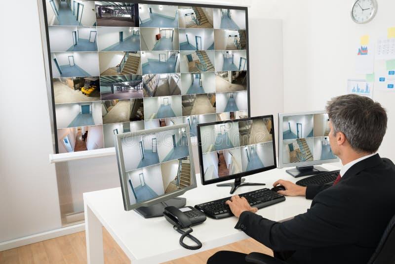 Homem na sala de comando que olha a metragem do cctv imagem de stock