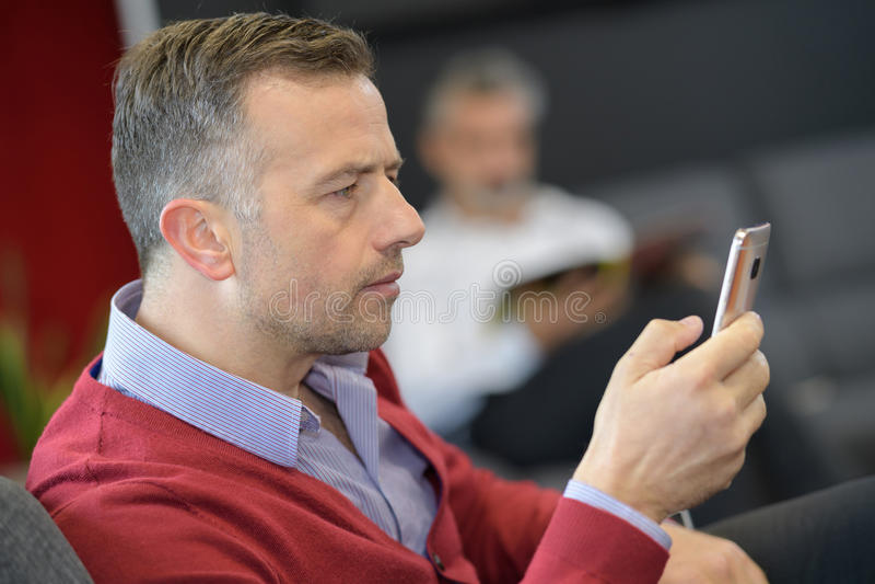 Homem na sala de espera que olha o telefone fotografia de stock