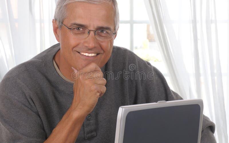 Homem na sala de visitas com computador fotografia de stock royalty free