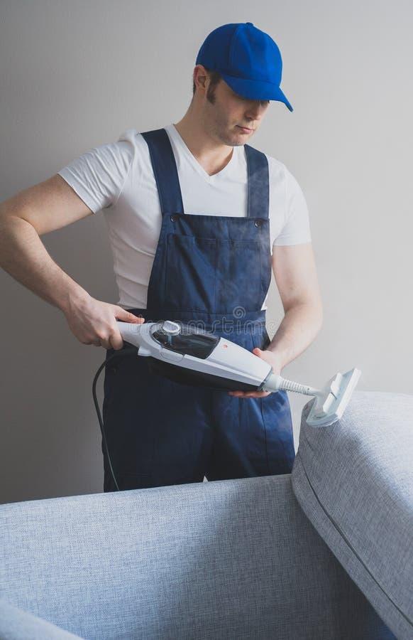 Homem na tela uniforme da limpeza do sofá imagens de stock
