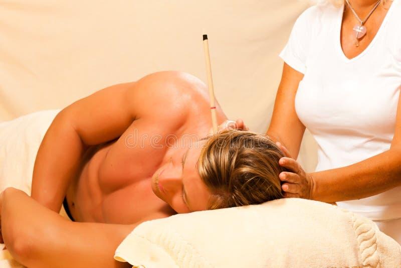Homem na terapia com velas da orelha imagem de stock royalty free