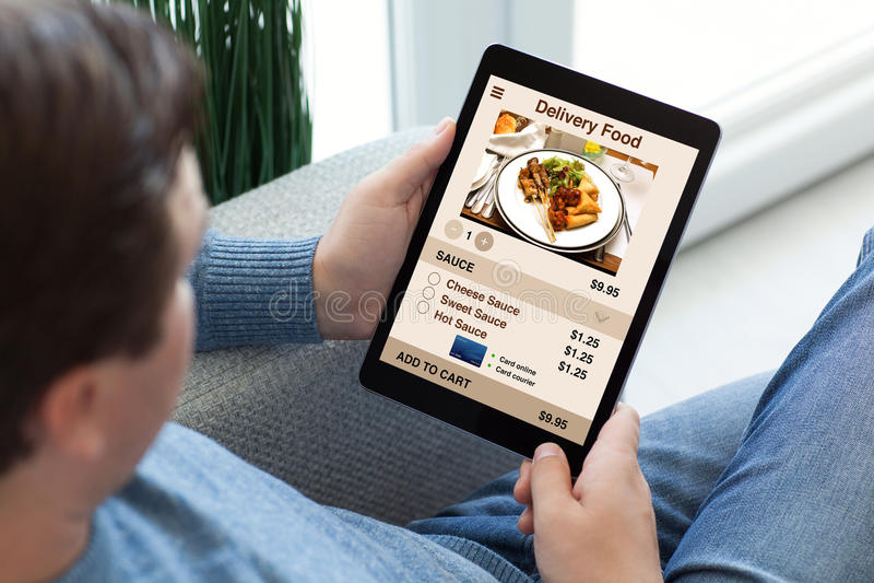 Homem nas calças de brim que guardam o tablet pc com alimento da entrega do app fotografia de stock royalty free