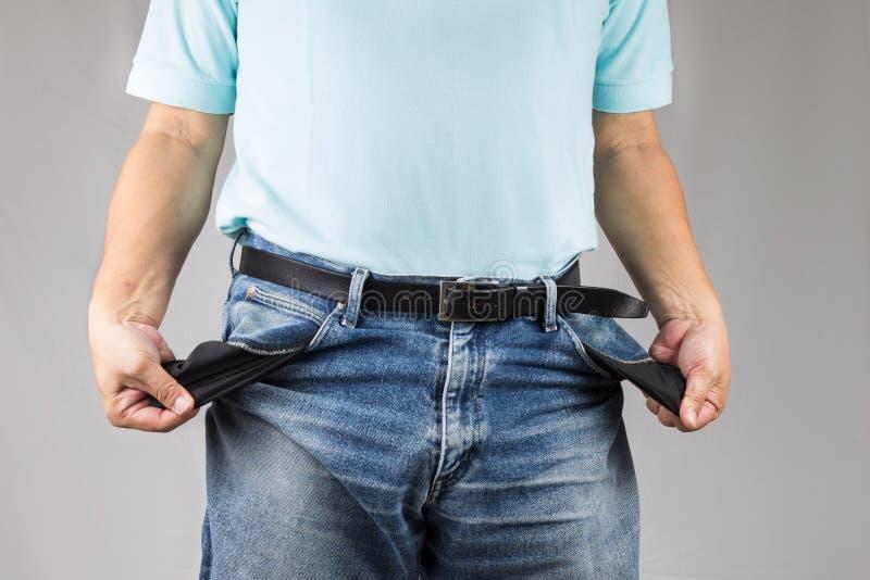 Homem nas calças de brim que retira seus bolsos vazios fotografia de stock