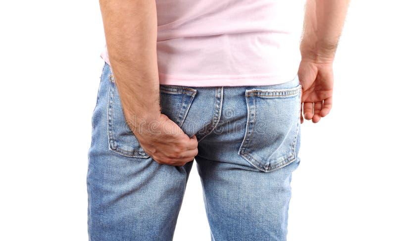 Homem nas calças de brim que riscam a mão sua parte inferior sarnento imagens de stock royalty free