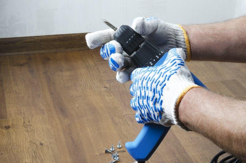 Homem nas luvas que preparam uma chave de fenda para trabalhos do reparo em casa Close up disparado com espaço vazio imagens de stock