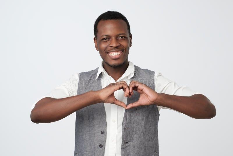 Homem negro africano que faz fora do coração das mãos Fazendo o trabalho da caridade fotos de stock