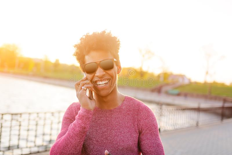 Homem negro brilhante que fala no telefone na luz imagem de stock