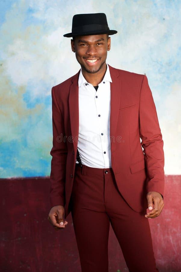 Homem negro considerável no terno do vintage e chapéu que sorriem pela parede foto de stock royalty free