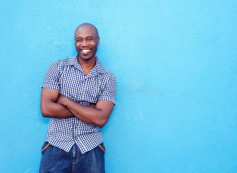 Homem negro considerável que sorri com os braços cruzados imagem de stock royalty free