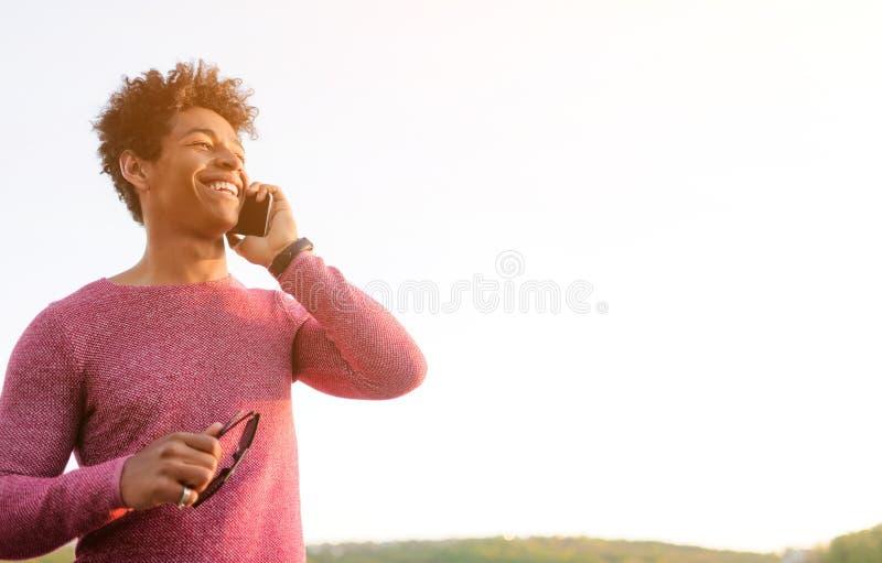 Homem negro de riso que fala no telefone na luz solar imagens de stock