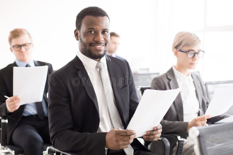 Homem negro de sorriso com os colegas na reunião fotografia de stock