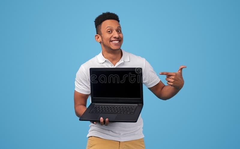 Homem negro de sorriso que mostra a boa oferta no portátil imagem de stock