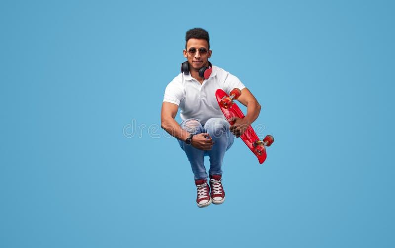Homem negro engraçado que salta com joelhos elaborados foto de stock royalty free