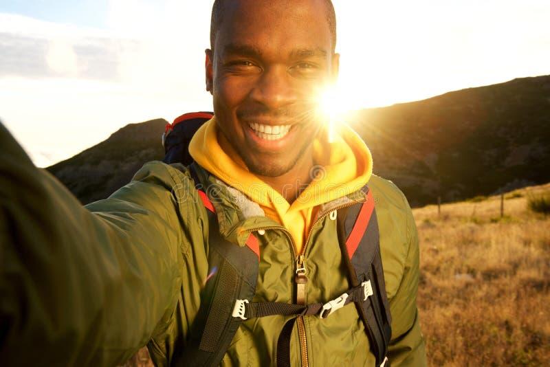Homem negro feliz que caminha e que toma o selfie com por do sol no fundo fotografia de stock