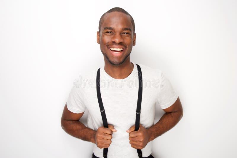 Homem negro feliz que levanta com os suspensórios contra o fundo branco fotografia de stock royalty free