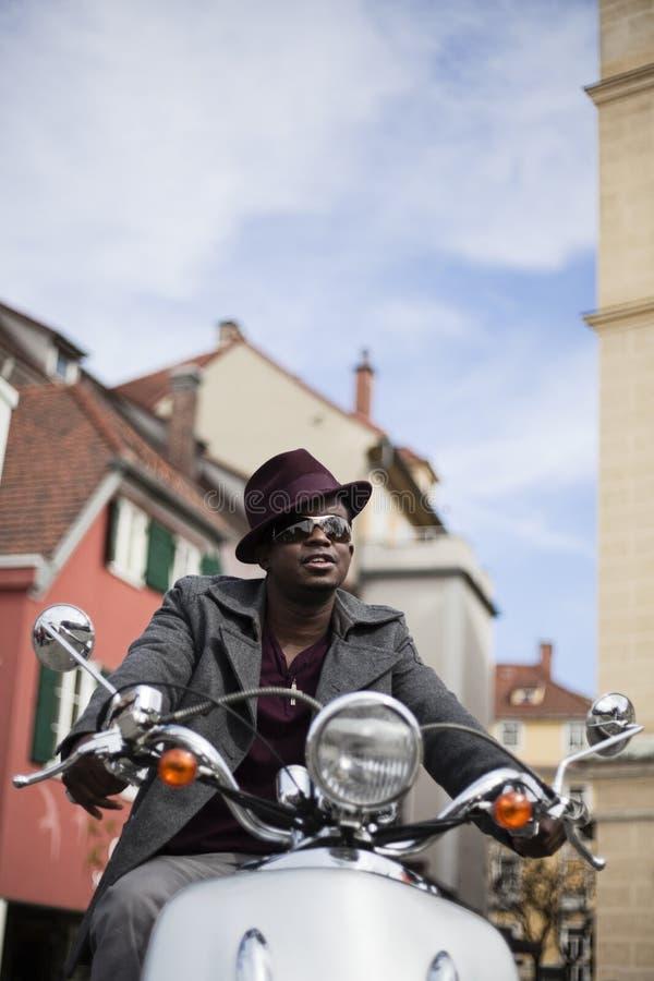 Homem negro fresco que monta um 'trotinette' imagem de stock
