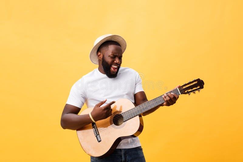 Homem negro muscular que joga a guitarra, calças de brim vestindo e a camiseta de alças branca Isolado sobre o fundo amarelo fotos de stock royalty free