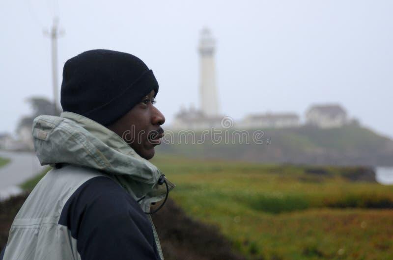 Homem negro na costa em um dia nevoento imagem de stock
