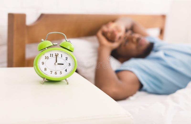 Homem negro no sofrimento da cama da desordem da insônia e de sono fotografia de stock royalty free