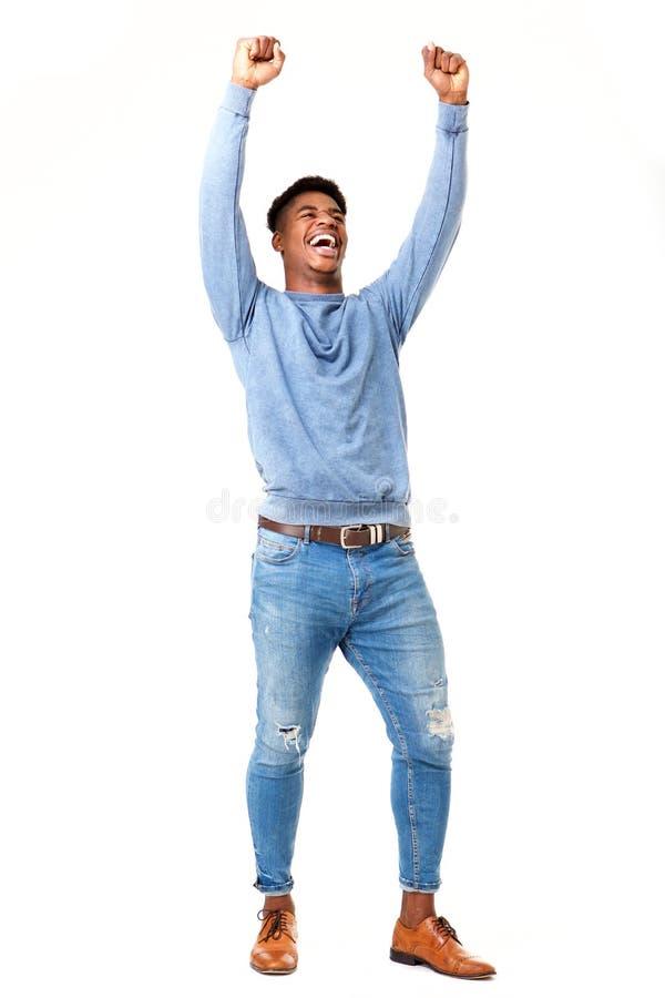 Homem negro novo alegre do corpo completo com os braços aumentados contra o fundo branco isolado foto de stock royalty free