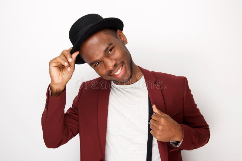 Homem negro novo atrativo que levanta com chapéu e blazer pelo fundo branco imagem de stock