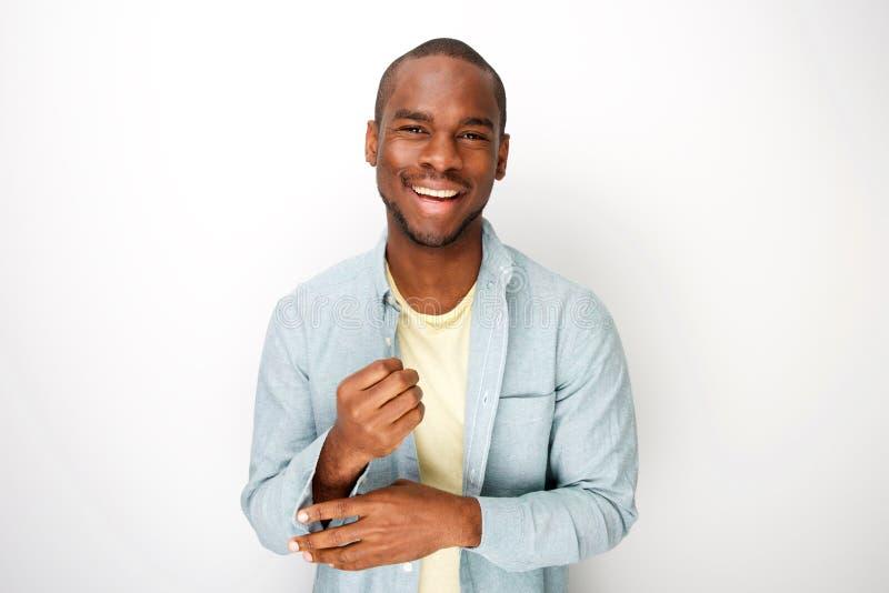 Homem negro novo atrativo que sorri com a camisa pelo fundo branco imagens de stock