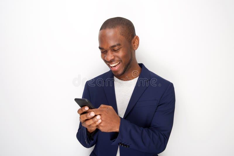 Homem negro novo considerável com o blazer que olha o telefone celular pelo fundo branco imagens de stock royalty free