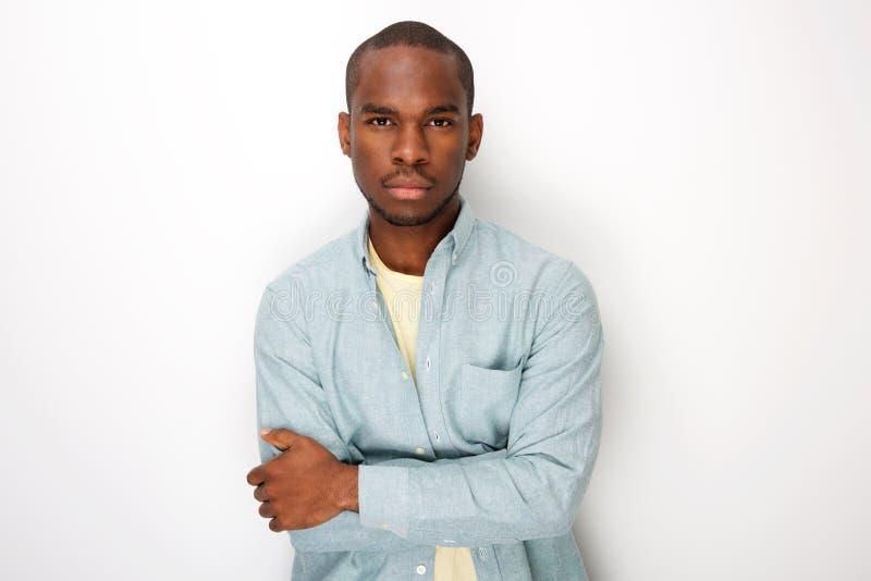 Homem negro novo considerável com os braços dobrados pelo fundo branco imagem de stock royalty free
