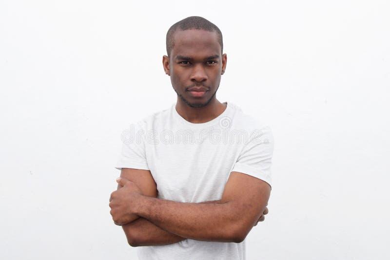 Homem negro novo considerável que levanta com os braços cruzados contra o fundo branco fotos de stock royalty free