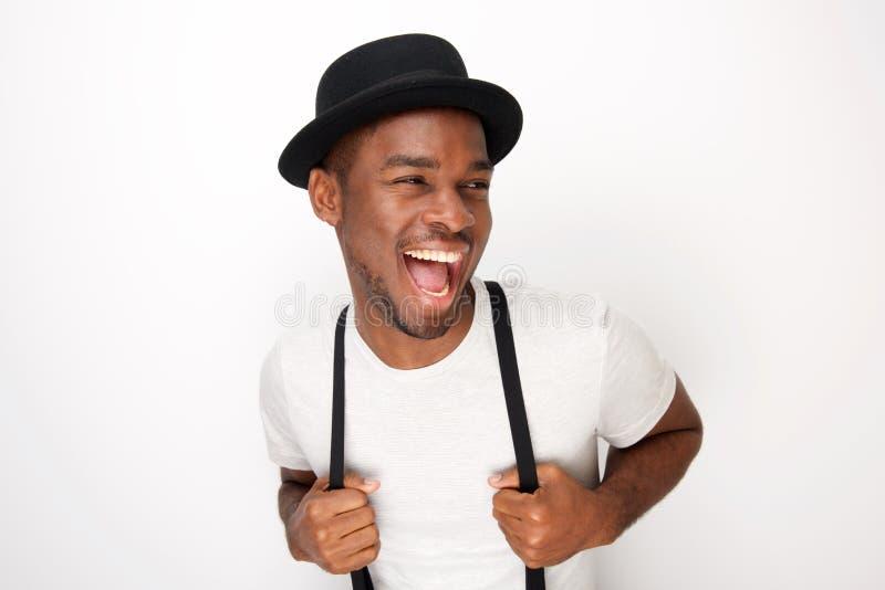 Homem negro novo considerável que ri com chapéu e suspensórios contra o fundo branco fotos de stock royalty free
