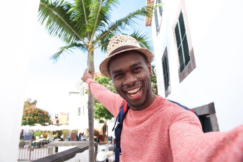 Homem negro novo considerável que sorri ao tomar o selfie em férias imagens de stock royalty free