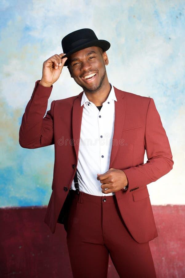 Homem negro novo considerável que sorri com o terno do chapéu e do vintage foto de stock royalty free