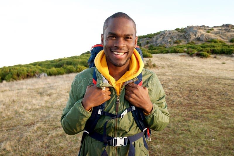 Homem negro novo de sorriso com posição da trouxa na natureza imagem de stock