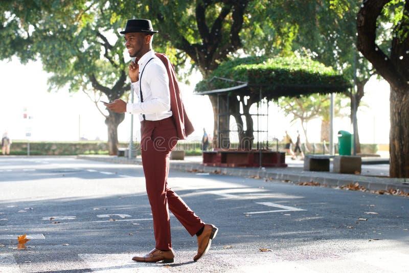 Homem negro novo de sorriso do comprimento completo no terno que anda com telefone celular na rua fotos de stock royalty free
