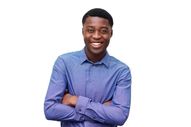 Homem negro novo de sorriso na camisa azul que levanta com os braços cruzados contra o fundo branco isolado fotografia de stock royalty free