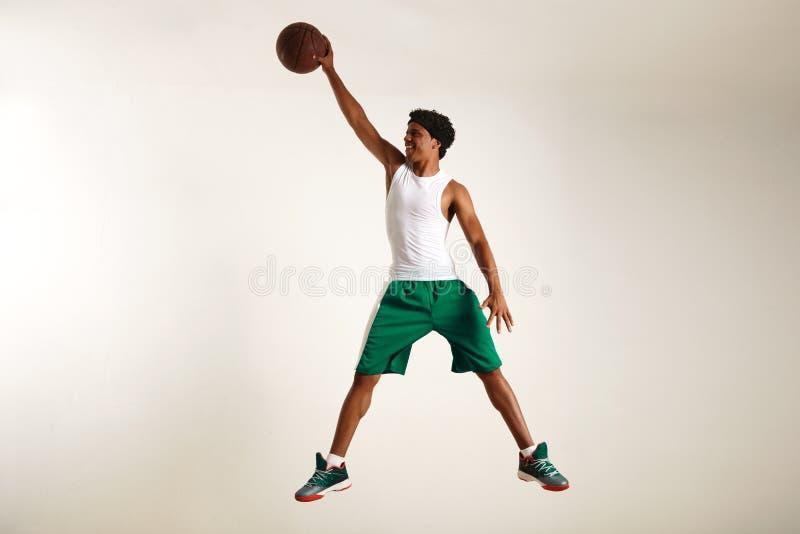 Homem negro novo de sorriso que alcança altamente para um basquetebol imagens de stock royalty free