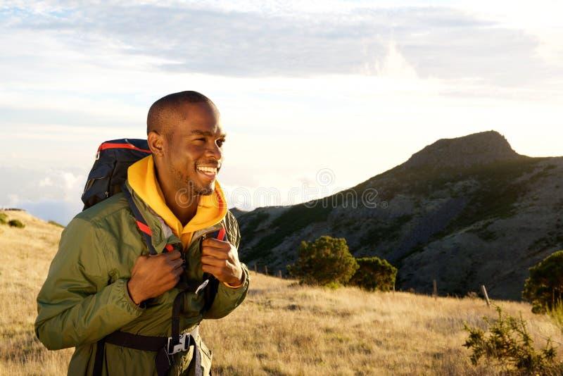 Homem negro novo de sorriso que caminha nas montanhas com saco da trouxa fotos de stock