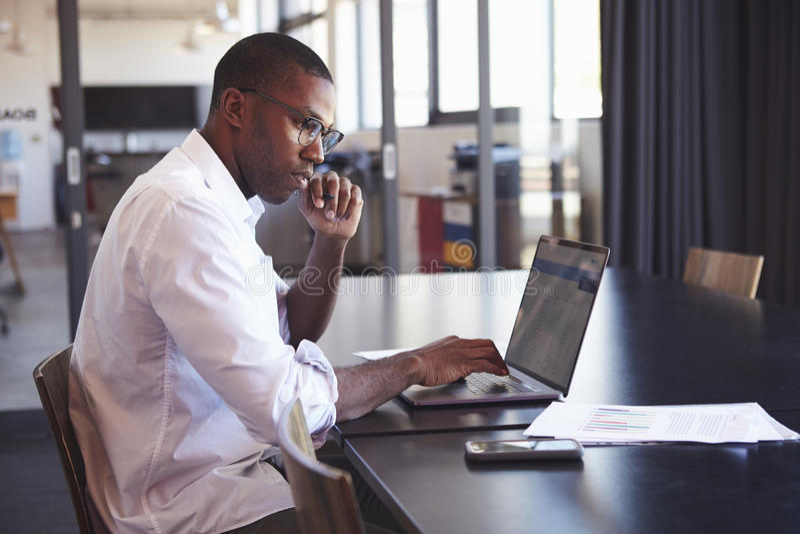 Homem negro novo em vidros vestindo usando o portátil no escritório imagens de stock