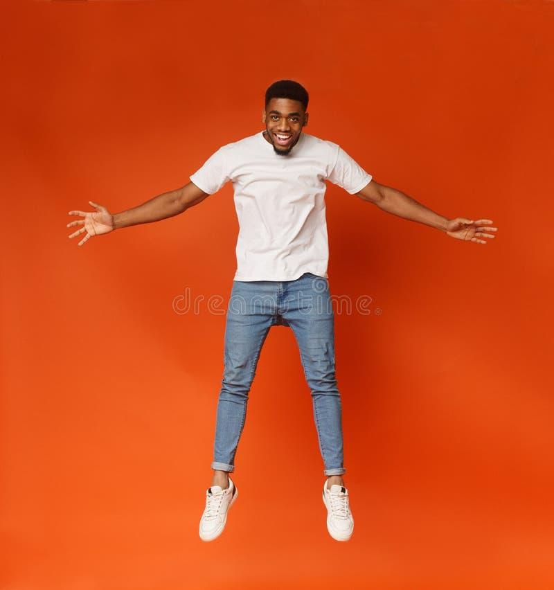 Homem negro novo engraçado que salta no ar fotos de stock
