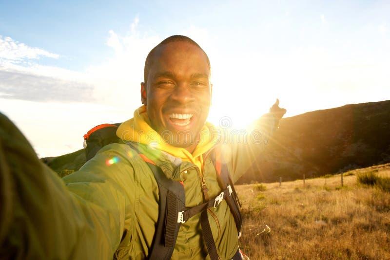 Homem negro novo feliz que caminha com a trouxa que toma o selfie e que aponta ao por do sol imagem de stock