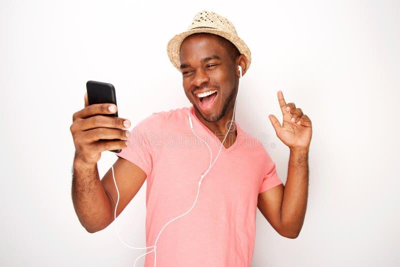 Homem negro novo feliz que escuta a música com fones de ouvido e dança foto de stock royalty free