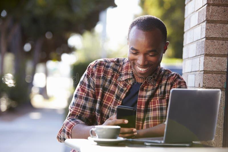 Homem negro novo fora de um café que olha seu smartphone fotografia de stock