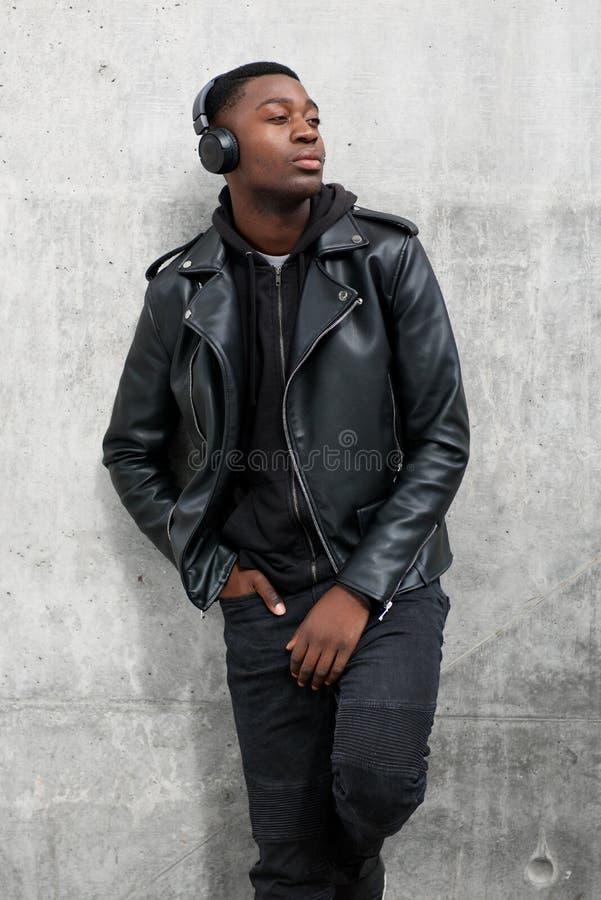 Homem negro novo fresco no casaco de cabedal que escuta a música com fones de ouvido imagens de stock royalty free